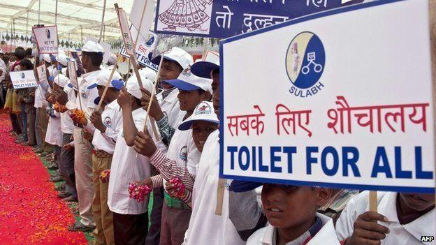 Indian schoolchildren hold placards as they welcome Bindeshwari Pathak, founder and chairman of NGO Sulabh International, at Katra Sahadatgunj village in Badaun on August 31, 2014