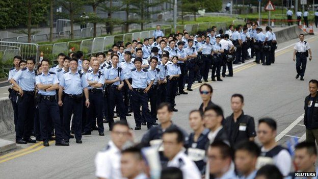 Police officers gather as protesters block the entrance to Hong Kong Chief Executive CY Leung's offices in Hong Kong on 2 October 2014