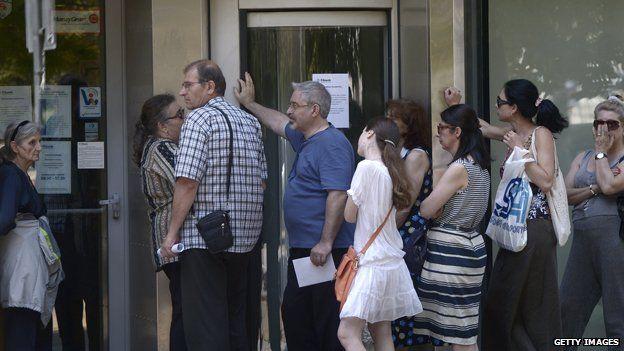 People queue to enter a bank