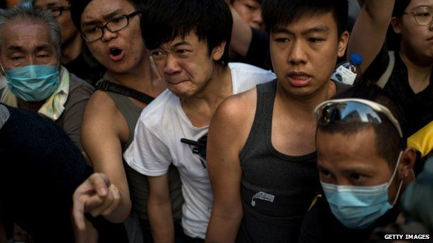 Pro-democracy demonstrators try to stop a barricade being removed at Causeway Bay - 3 October