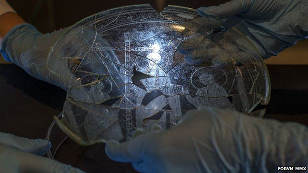 Hands holding an ancient plate
