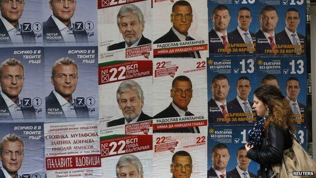 A woman walks past election posters in Sofia. Photo: 3 October 2014