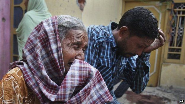 """Relatives of Rajesh Kumar, who was killed in mortar shell firing allegedly from the Pakistan""""s side, weep inside their residential house at Masha da kothe village, in Arnia Sector near the India-Pakistan international border, about 47 kilometers (30 miles) from Jammu, India, Monday, Oct. 6, 2014."""