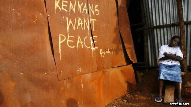 A woman rests near her shack in the Kibera slums painted with a peace statement on 10 February 2008 in Nairobi, Kenya