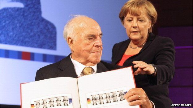 Former German Chancellor Helmut Kohl and German Chancellor Angela Merkel pose with stamps featuring Mr Kohl in Berlin on 27 September 2012