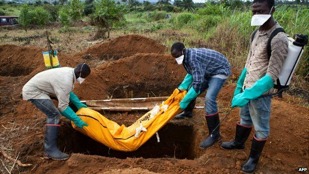 Volunteers in protective suit bury the body of an Ebola victim in Waterloo, 30km southeast of Freetown, Sierra Leone - 7 October 2014
