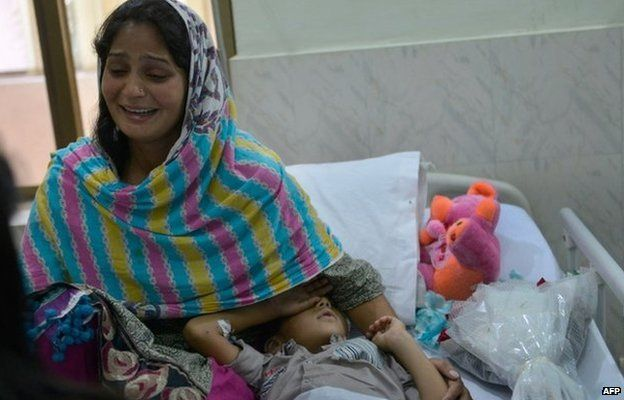Iram Shahzadi sits with her son in a Pakistani hospital
