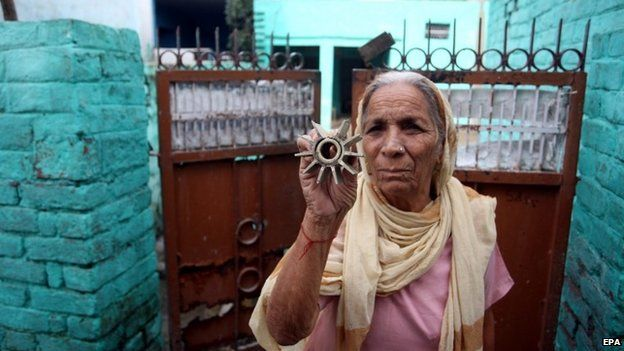 An Indian villager displays parts of mortar shells allegedly fired from the Pakistani side of the disputed Kashmir border, at Arnia Village
