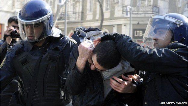 Two policemen lead away a protester in Baku in Azerbaijan