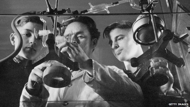 Two German boys watch a scientist perform an experiment