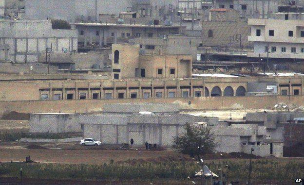 Islamic State gunmen crouch during fighting in Kobane, 11 October (photo taken with long-range lens)