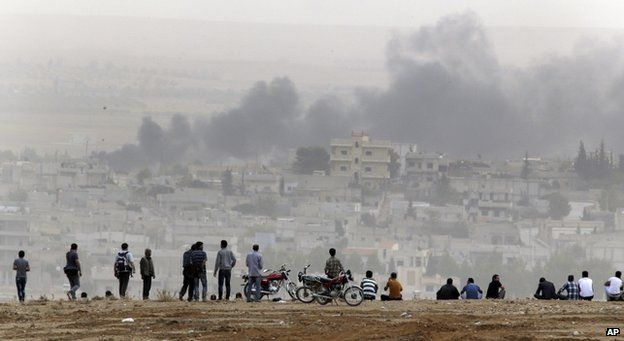 Civilians watch the fighting in Kobane from the safety of the Turkish side of the border, 11 October