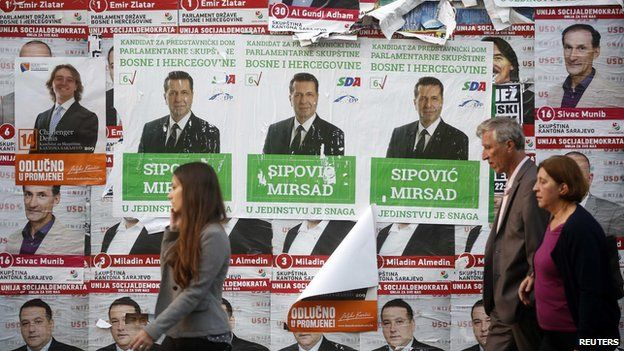 People walk past election posters in Sarajevo, October 10, 2014