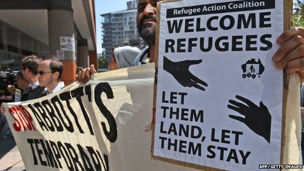 A protestor holds up a pro-refugee placard at a rally