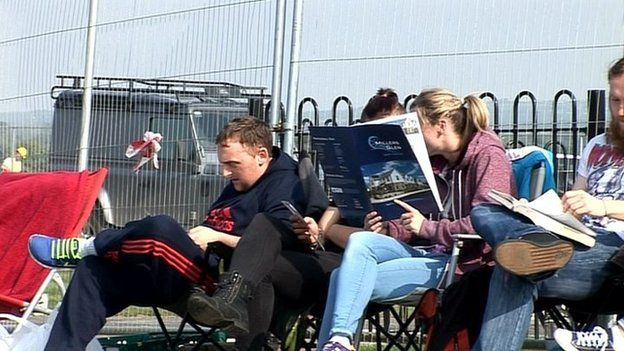 People are sitting in deck chairs queuing to buy houses and apartments in a new development