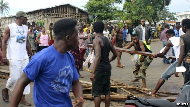 Residents place roadblocks on the street to demand faster removal of dead bodies infected with Ebola virus in the Aberdeen district of Freetown, Sierra Leone, on 14 October 2014.