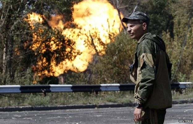 An armed pro-Russian separatist looks as flames erupt from a gas pipeline after a shelling in Donetsk (August 2014 file pic)