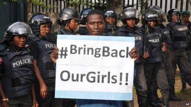 A man poses with a sign in front of police officers in riot gear during a demonstration calling on the government to rescue the kidnapped girls from Chibok, in Abuja, on 14 October 2014.