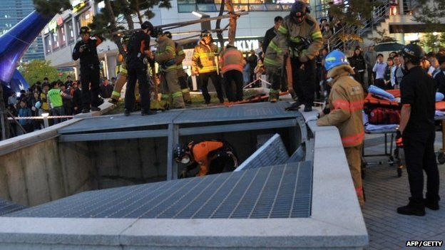 Rescue workers inspect the broken ventilation grate in Seongnam City, South Korea on 17 October 2014