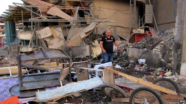 Iraqis inspect the scene of a car bomb attack at Karada district in central Baghdad, Iraq, 18 October 2014