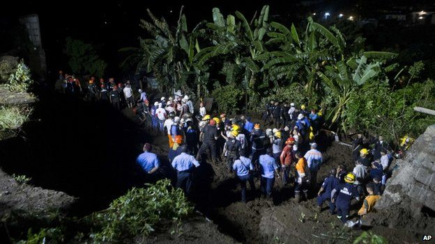 Rescuers workers search for bodies after a wall that collapsed during heavy rain in Managua, Nicaragua, early Friday, Oct. 17, 2014