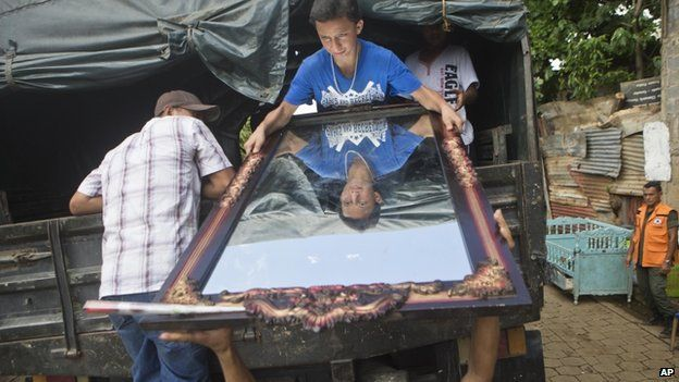 A young man helps to load a mirror onto to a truck during an evacuation of residents from the 18 de Mayo neighbourhood where nine people died when a wall collapsed in heavy rains, in Managua, Nicaragua, Friday, Oct. 17, 2014.