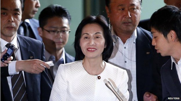 Japan's Justice Minister Midori Matsushima (C) reacts as she is surrounded by reporters upon her arrival at Prime Minister Shinzo Abe's official residence for a meeting with Abe in Tokyo 20 October 2014