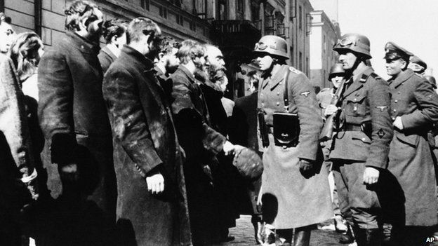 Nazi officers talk to people living in a ghetto in Warsaw, Poland, in 1943