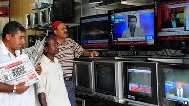 Pakistani viewers watch television news broadcasts at an electrical store in Karachi, Pakistan on 2 May 2011