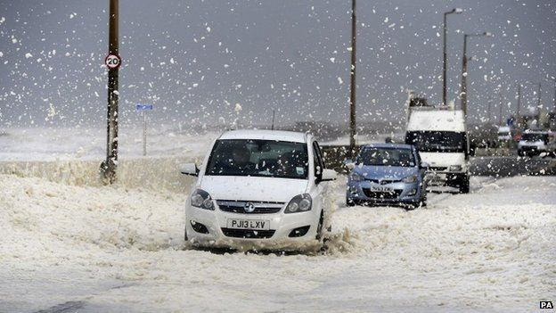 Foam from large waves and whipped up by gale force winds cover the coast road at Cleveleys
