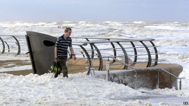 man walking through waves
