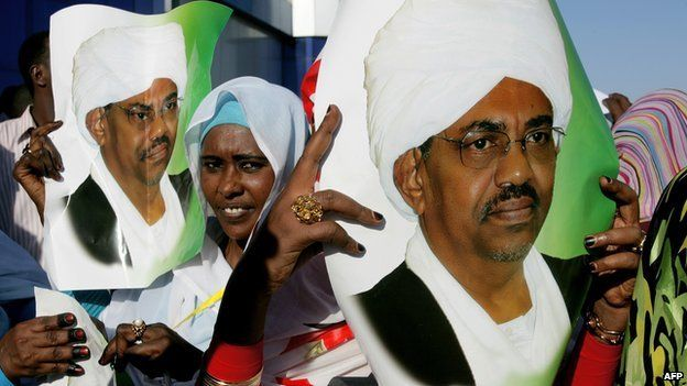 Supporters of Sudanese President Omar al-Bashir hold his pictures as they wait to greet him at Khartoum airport on 14 November 2012