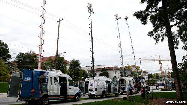 Television satellite vans park outside Emory University Hospital in Atlanta, Georgia.