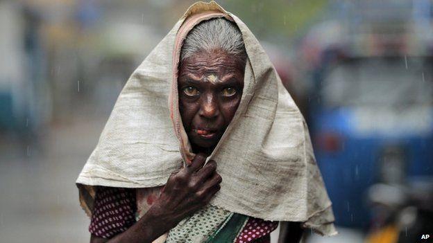 A Sri Lankan ethnic Tamil woman walks in the rain in Colombo, Sri Lanka, Friday, 22 August 2014.