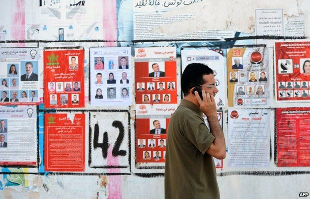 A Tunisian speaks on the phone as he walks past election posters put up on a street ahead of the parliamentary election in the Tunis suburb of Ariana on October 21, 2014.