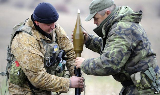 Ukrainian soldiers load a grenade launcher at their position in the village of Bugas in the Donetsk region, on 24 October 2014