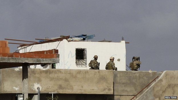 Tunisian security forces seen in the balcony of a house near to where gunmen were holed up in Oued Ellil, west of Tunis, on 24 October 2014.