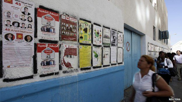 People look at parliamentary election posters in Tunis October 22, 2014. Tunisians go to the polls on October 26 for their second free parliamentary election.