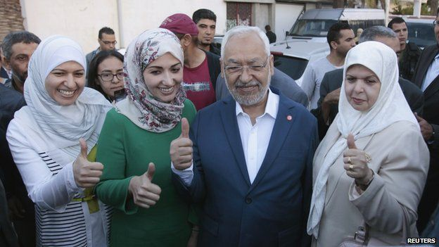 Rached Ghannouchi (C), leader of the Tunisian Islamist party Ennahda, gestures with his wife and two daughters Yousra (L) and Soumaya (2nd L) at a polling station during an election in Tunisia October 26, 2014