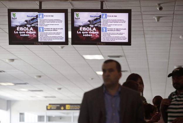 Passengers stand underneath screens explaining Ebola symptoms at Tocumen International Airport in Panama City