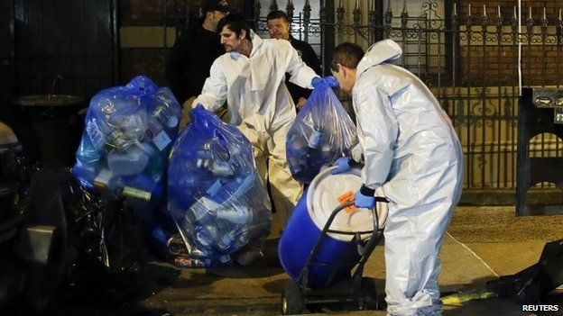 """Members of a cleaning crew with """"Bio Recovery Corporation"""" wearing personal protective equipment (PPE) push a barrel to be loaded in a truck of Centers for Disease Control and Prevention (CDC) after cleaning the apartment where Dr. Craig Spencer lives in New York October 24, 2014."""