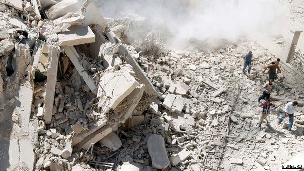 """Residents look for survivors under the rubble of collapsed buildings after what activists said was a vacuum bomb dropped by forces of Syria""""s President Bashar al-Assad on Maarat Al-Nouman, south of Idlib September 18, 2014"""