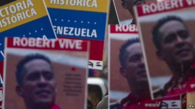 Posters showing images of murdered Venezuelan lawmaker Robert Serra during a march in Caracas on 18 October 2014.