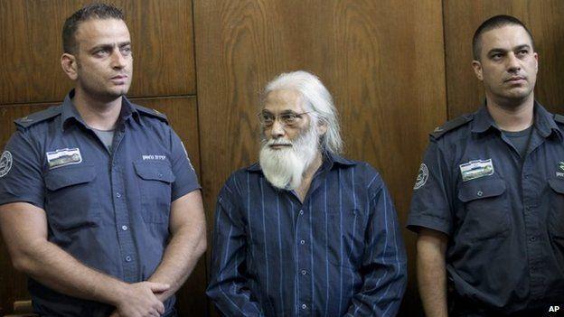 Goel Ratzon stands in between police officers in court