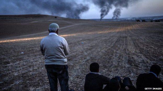 A Kurdish man prays as smokes rises from the town of Kobane, near the Turkish border with Syria.