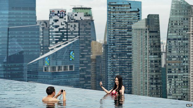 A couple take their photo from the Marina Bay Sands swimming pool overlooking Singapore's business district