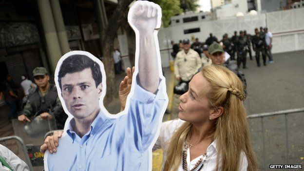 The wife of arrested opposition leader Leopoldo Lopez, Lilian Tintori, holds a poster of her husband in front of the Venezuelan courthouse in Caracas on 23 July, 2014.