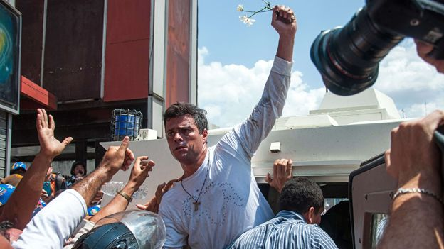 Leopoldo Lopez is escorted by the national guard into a vehicle after he turned himself in on 18 February, 2014
