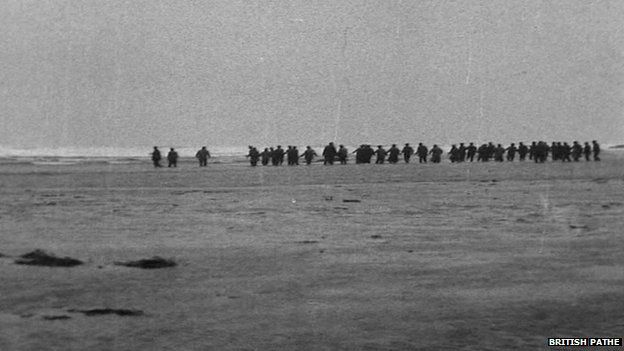 Crowds forming a line on the beach to wade out to help survivors of the Rohilla