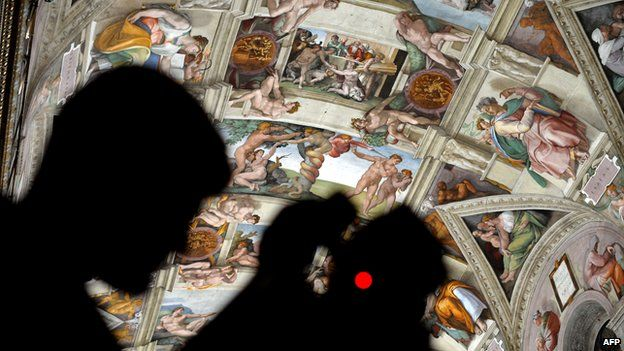 A journalist takes a picture inside the Sistine Chapel after its new lights and AC are installed